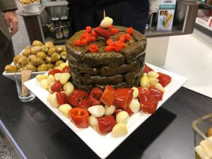 A Dolma Tower Surrounded By Companion Red Peppers & Garlic-Visually Delicious & Compels Sales